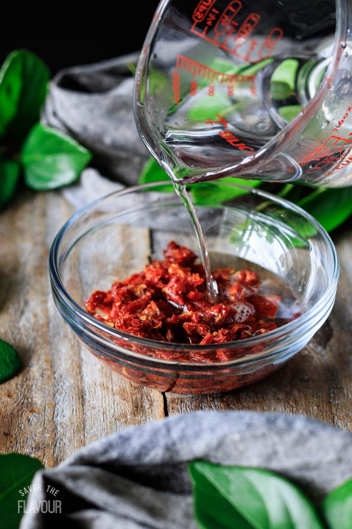pouring water on chopped sun dried tomatoes