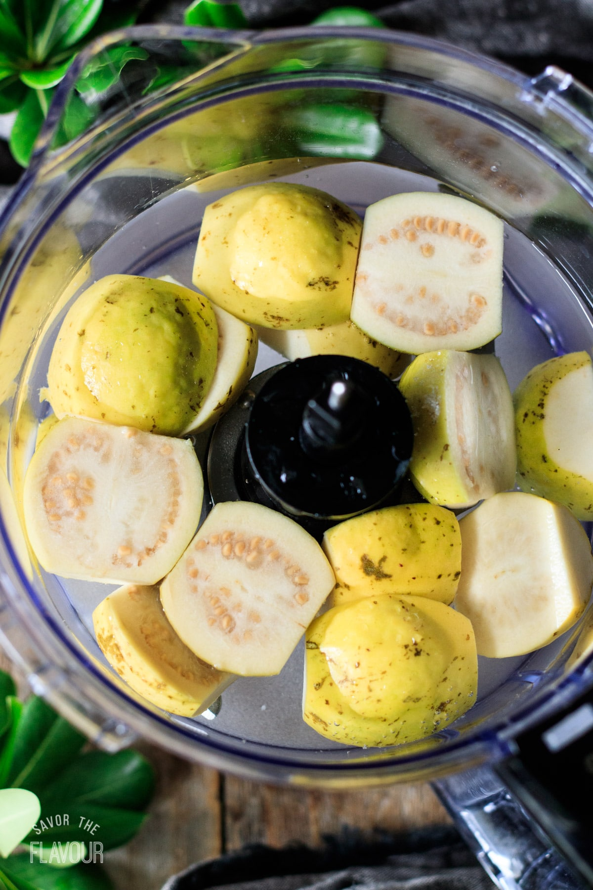 halved guavas and water in a food processor