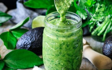 person pouring a spoonful of avocado cilantro dressing into a jar