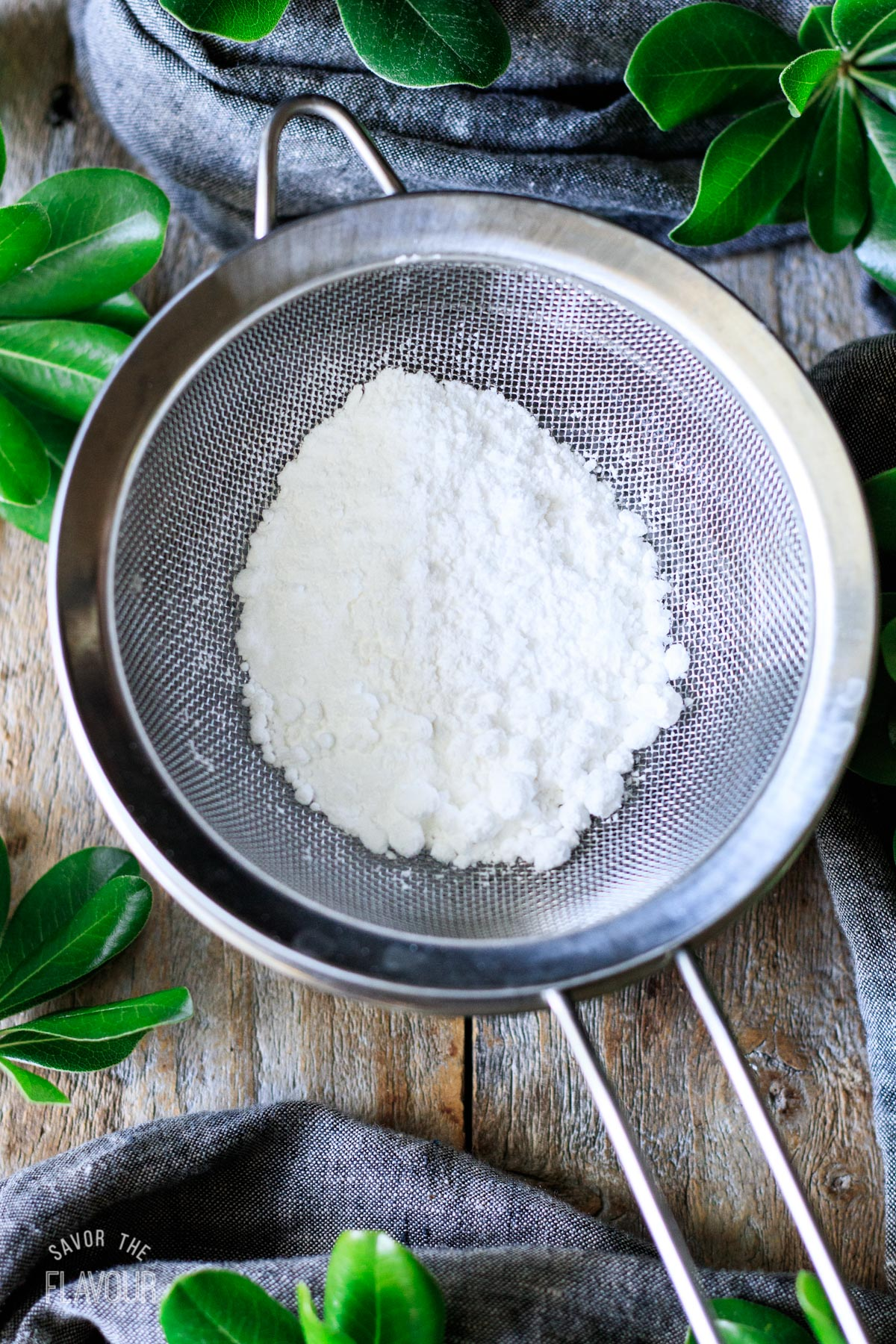 sifting powdered sugar into a small bowl