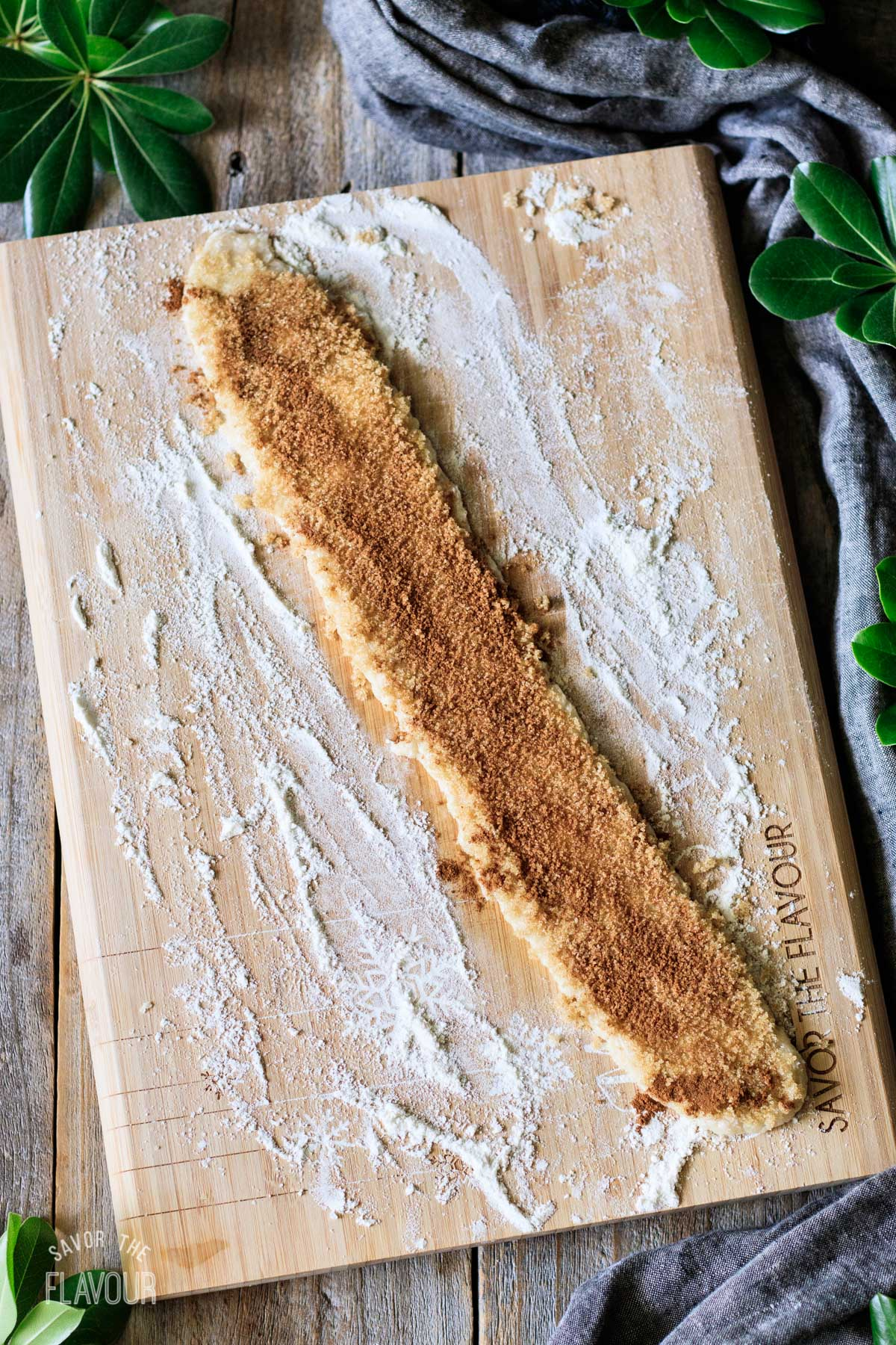 dough sprinkled with cinnamon sugar on a cutting board