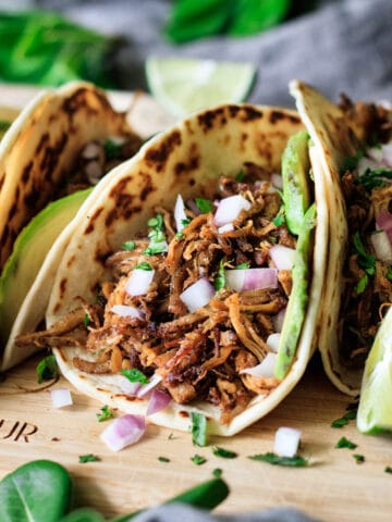 Chipotle pork carnitas with lime wedges