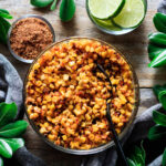 bowl of roasted corn kernels with spices and lime