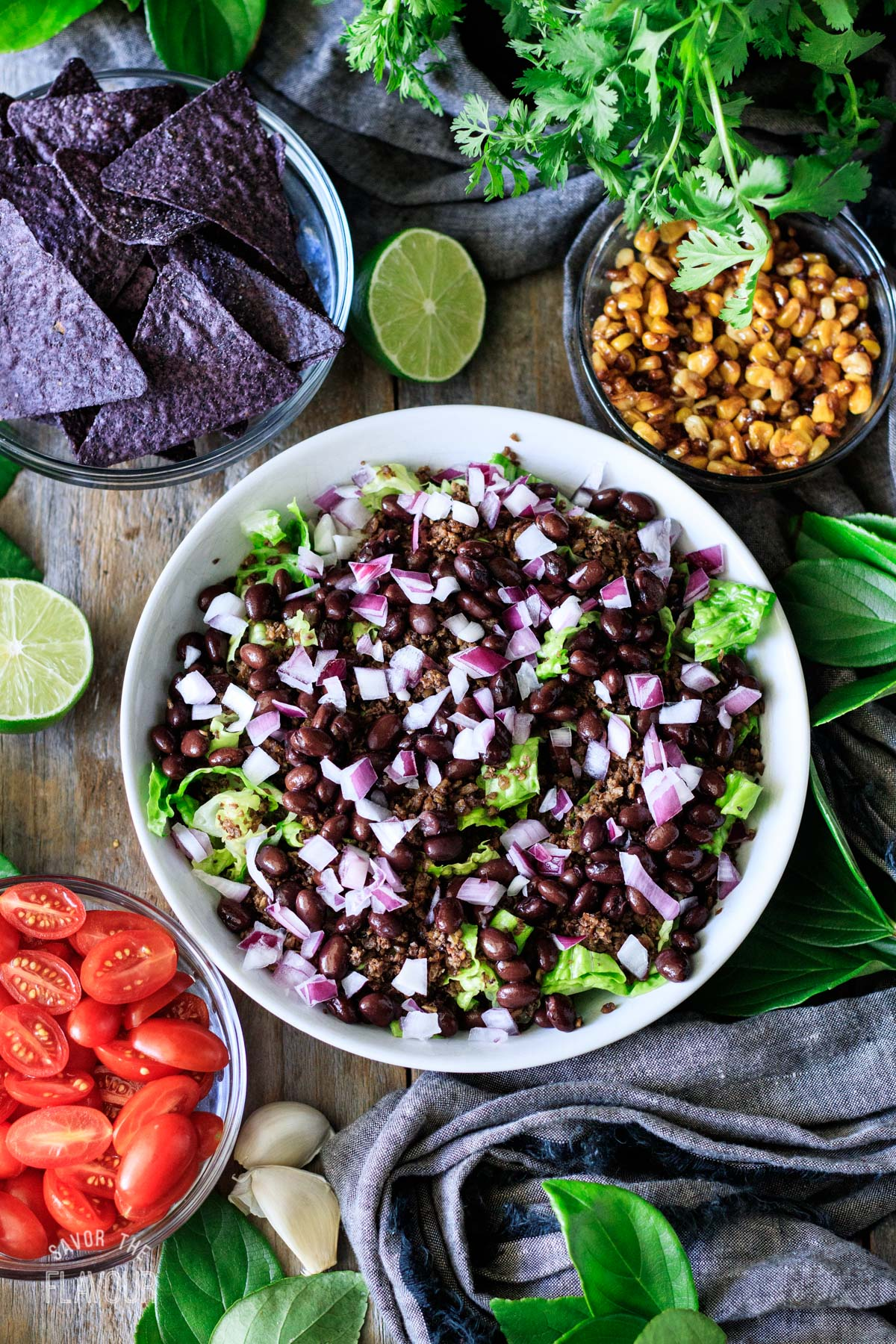 adding black beans and red onion to the taco salad