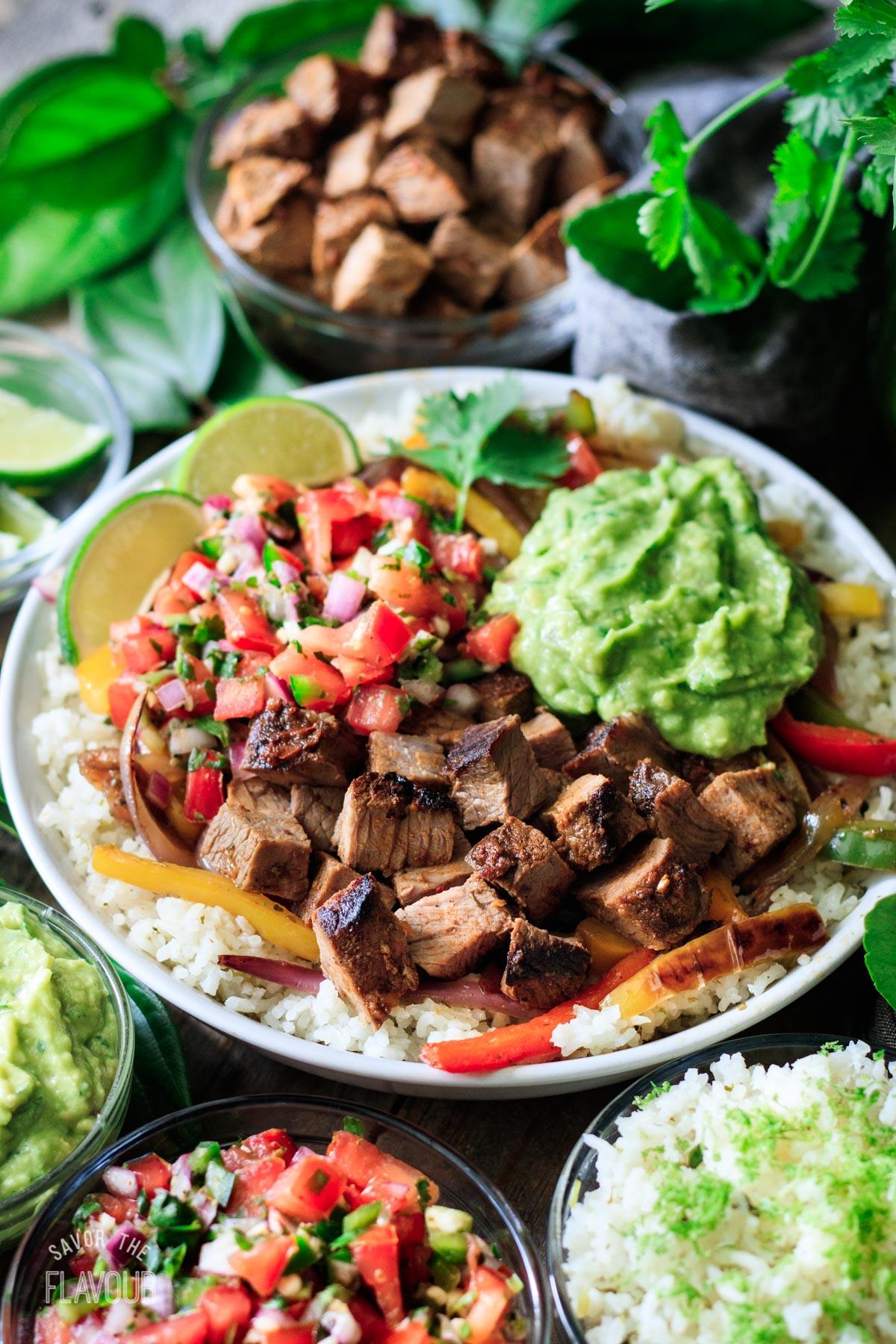 Chipotle steak in a bowl with rice, guac, and pico de gallo