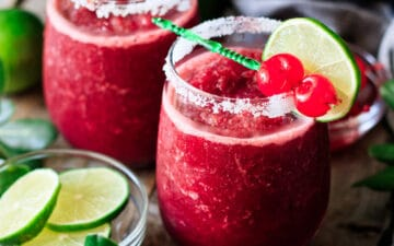 two glasses of frozen cherry limeade with a bowl of lime slices
