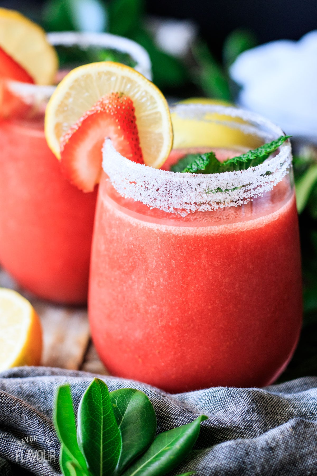 glass of frozen strawberry lemonade garnished with lemon, strawberry, and mint