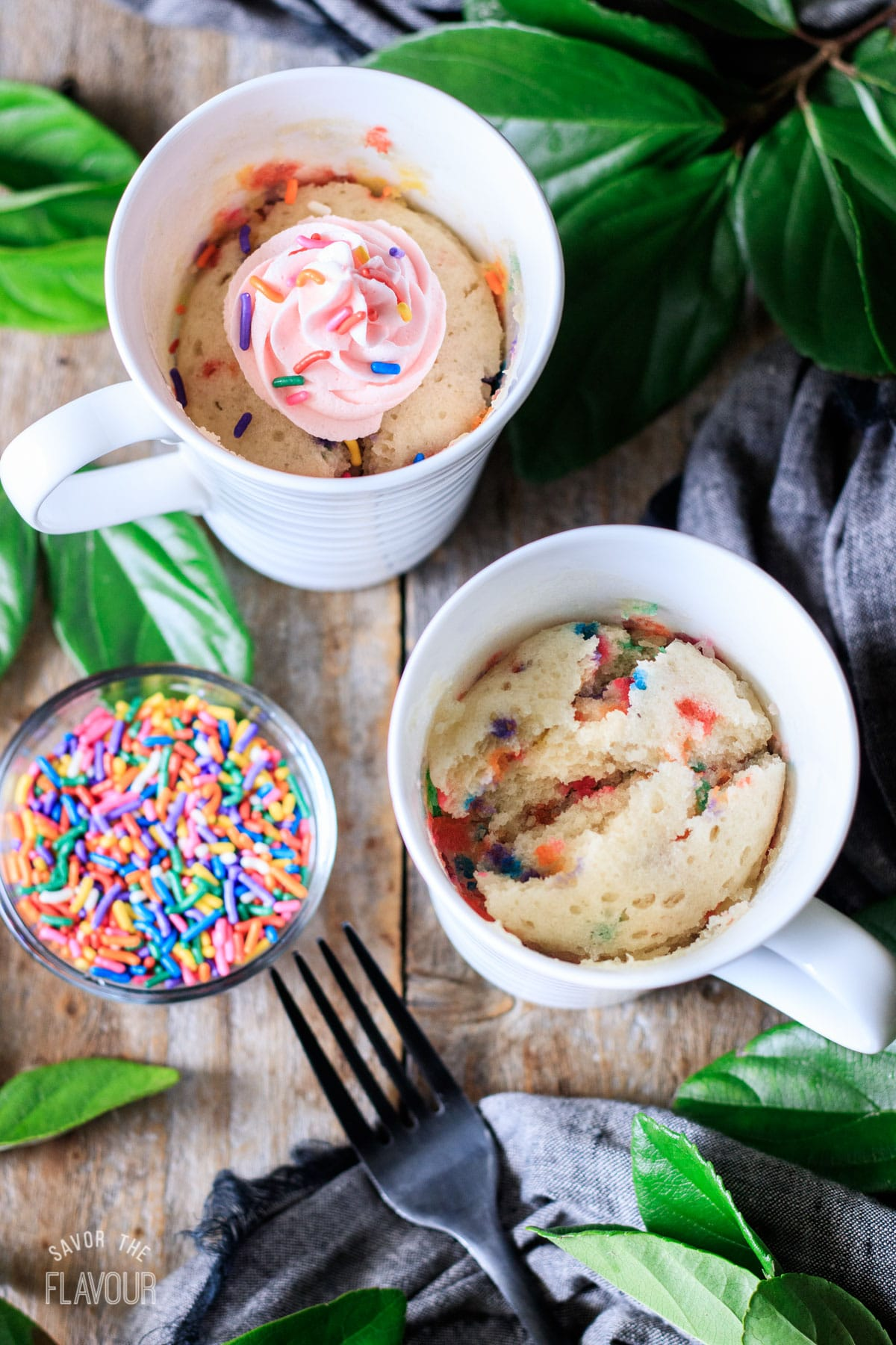 two cooked funfetti mug cakes in white mugs