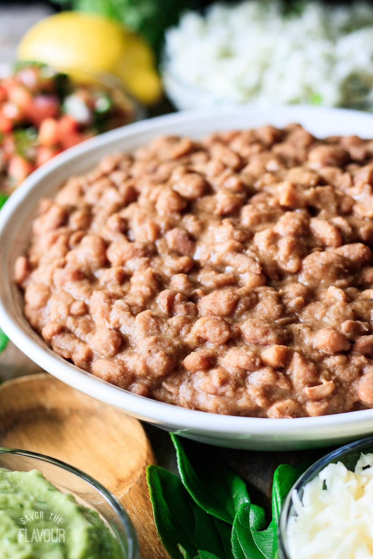 a bowl of Chipotle pinto beans with a wooden spoon