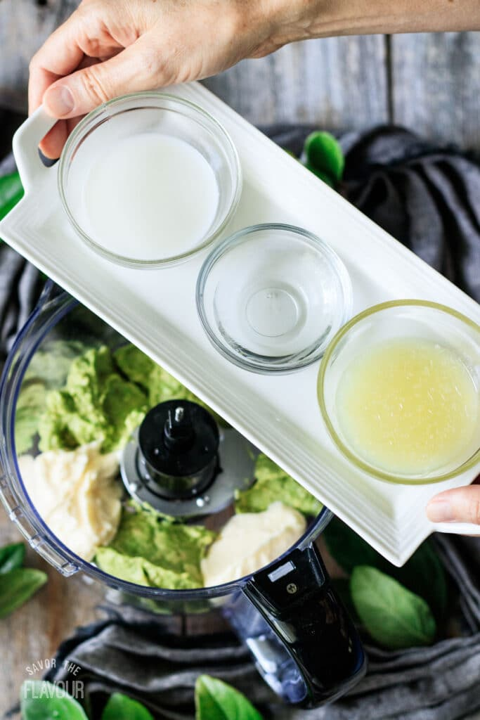 person holding a tray of milk, vinegar, and lime juice