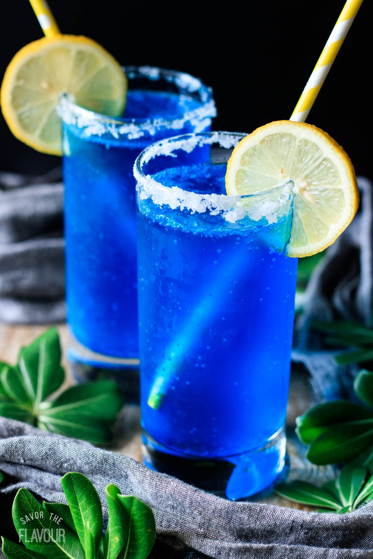 two blue lagoon mocktails with paper straws