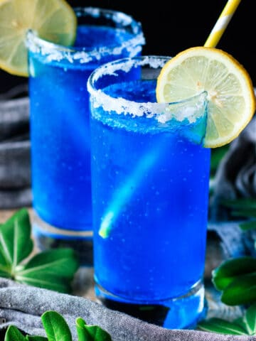 two blue lagoon mocktails with lemon slices