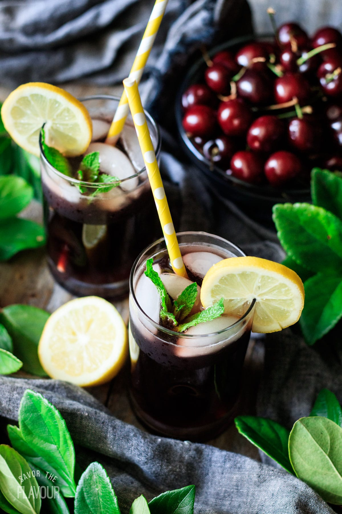 two glasses of cherry lemonade garnished with mint and lemon