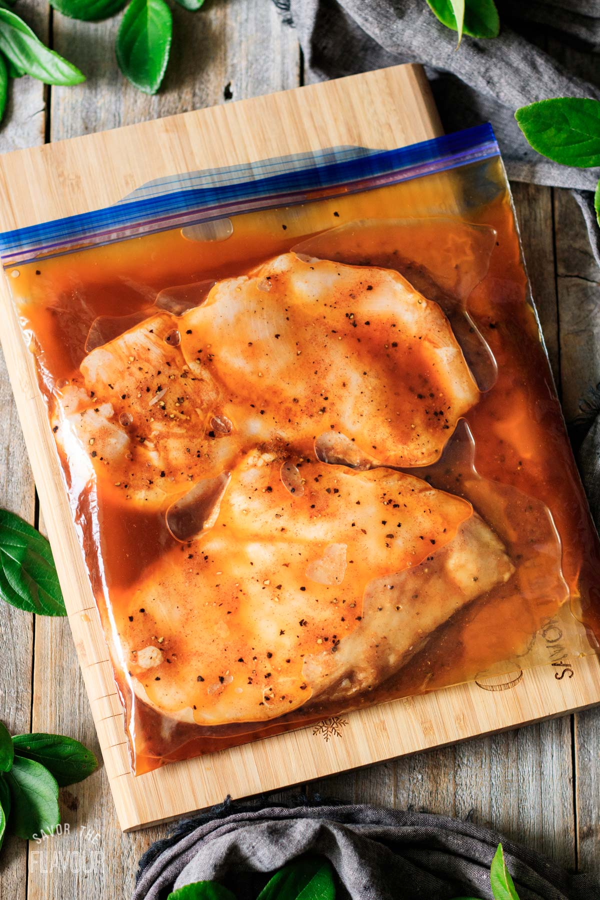 two chicken breasts marinating in a zip-top bag