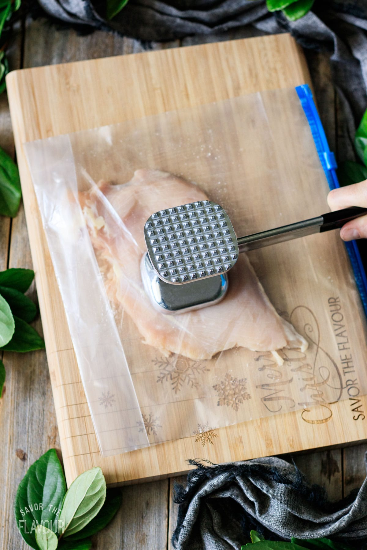 person pounding chicken with a meat mallet