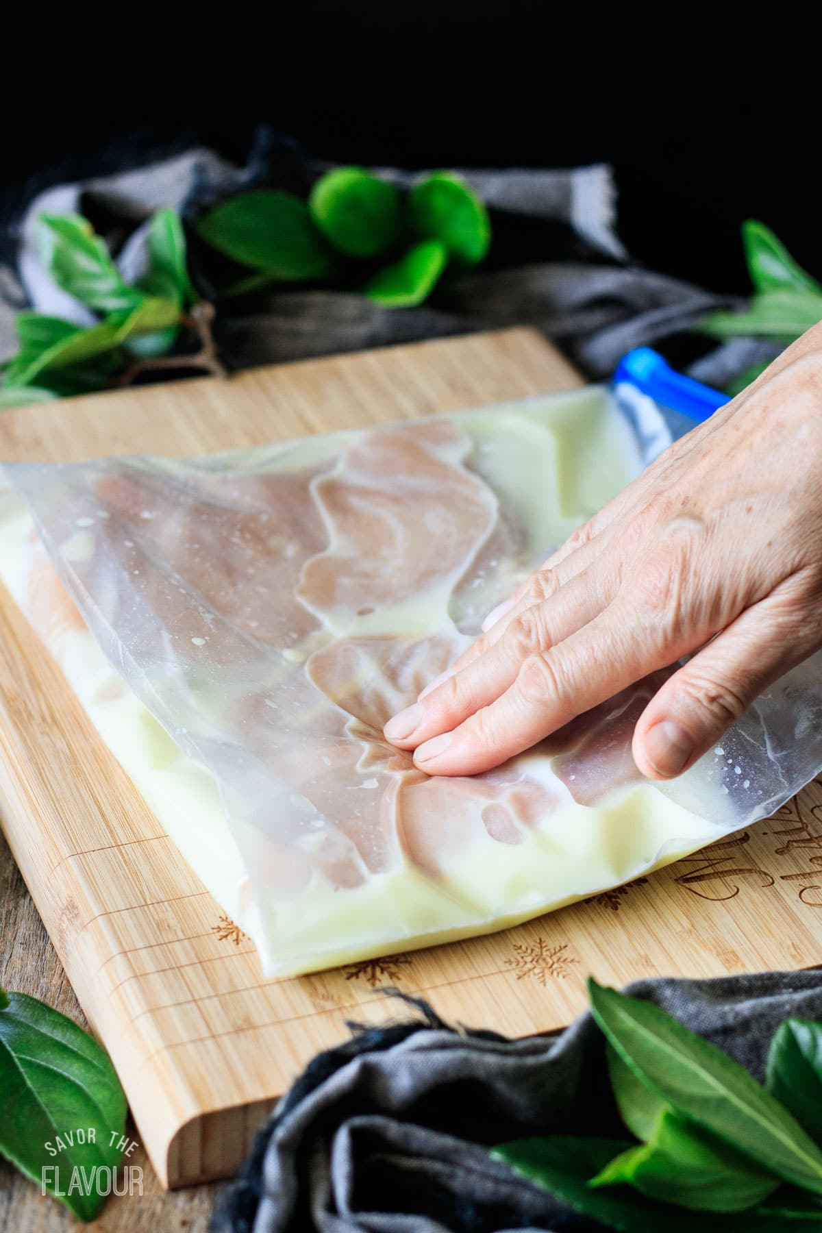 person patting a bag of chicken with brine