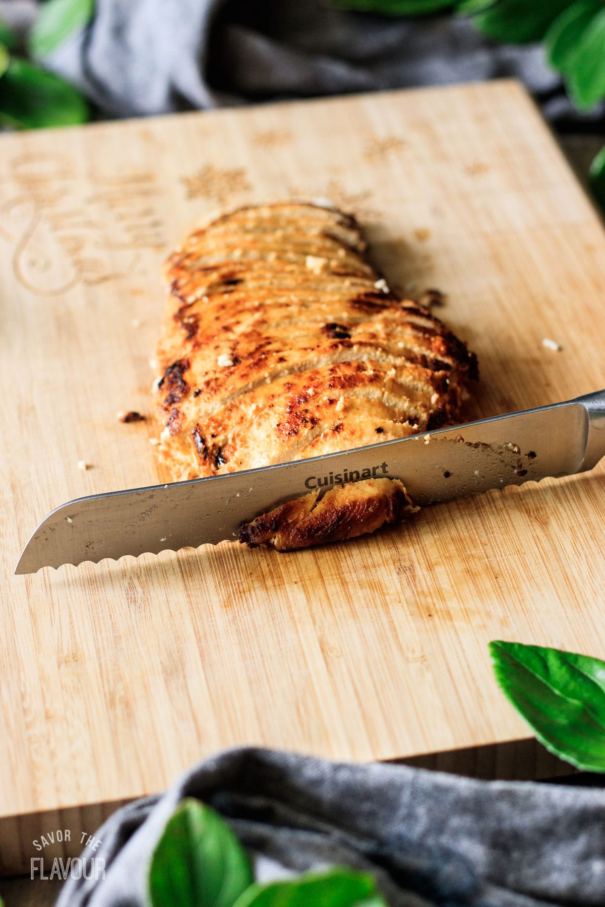 slicing the cooked chicken breast with a serrated knife