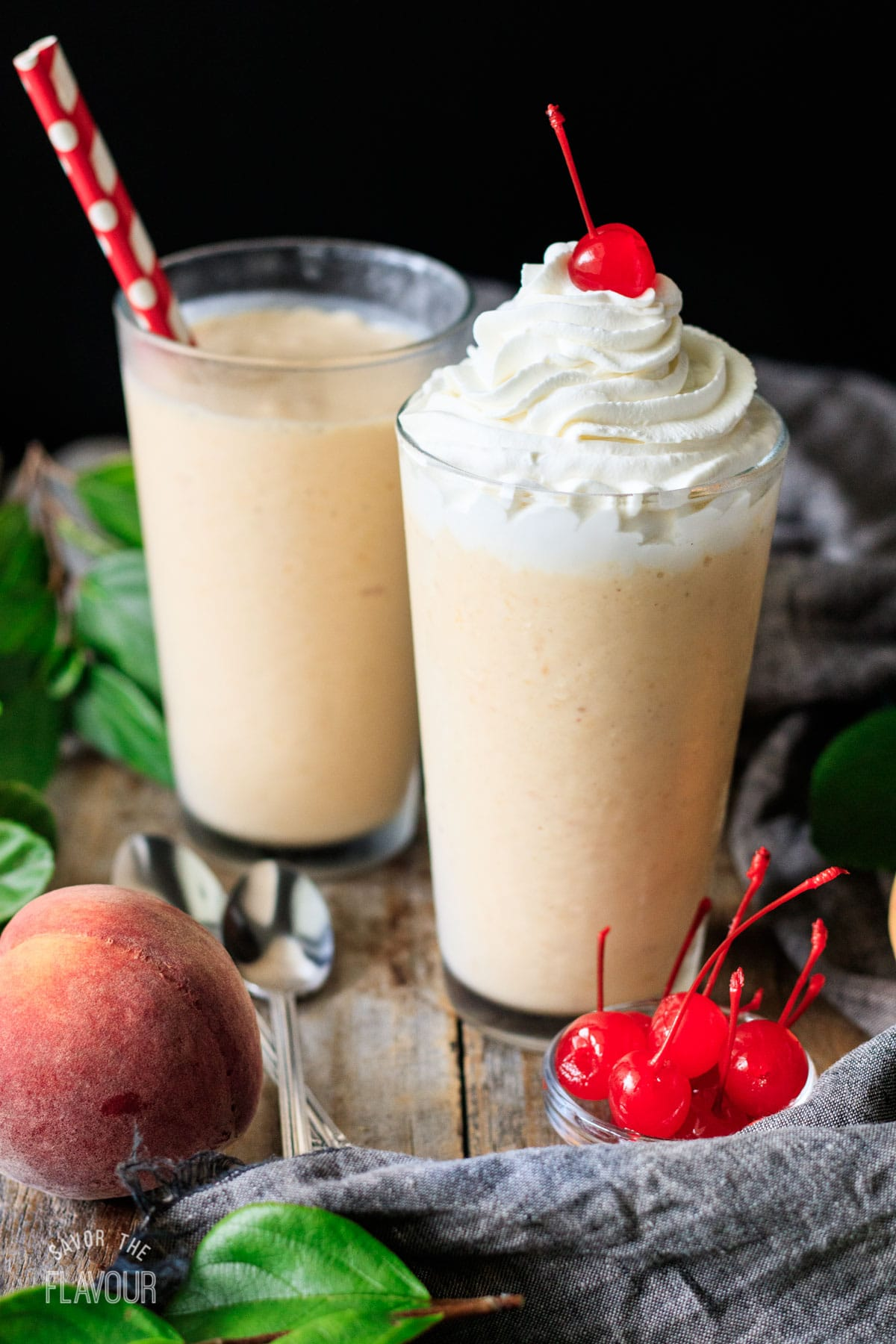 a peach milkshake with whipped cream and a cherry