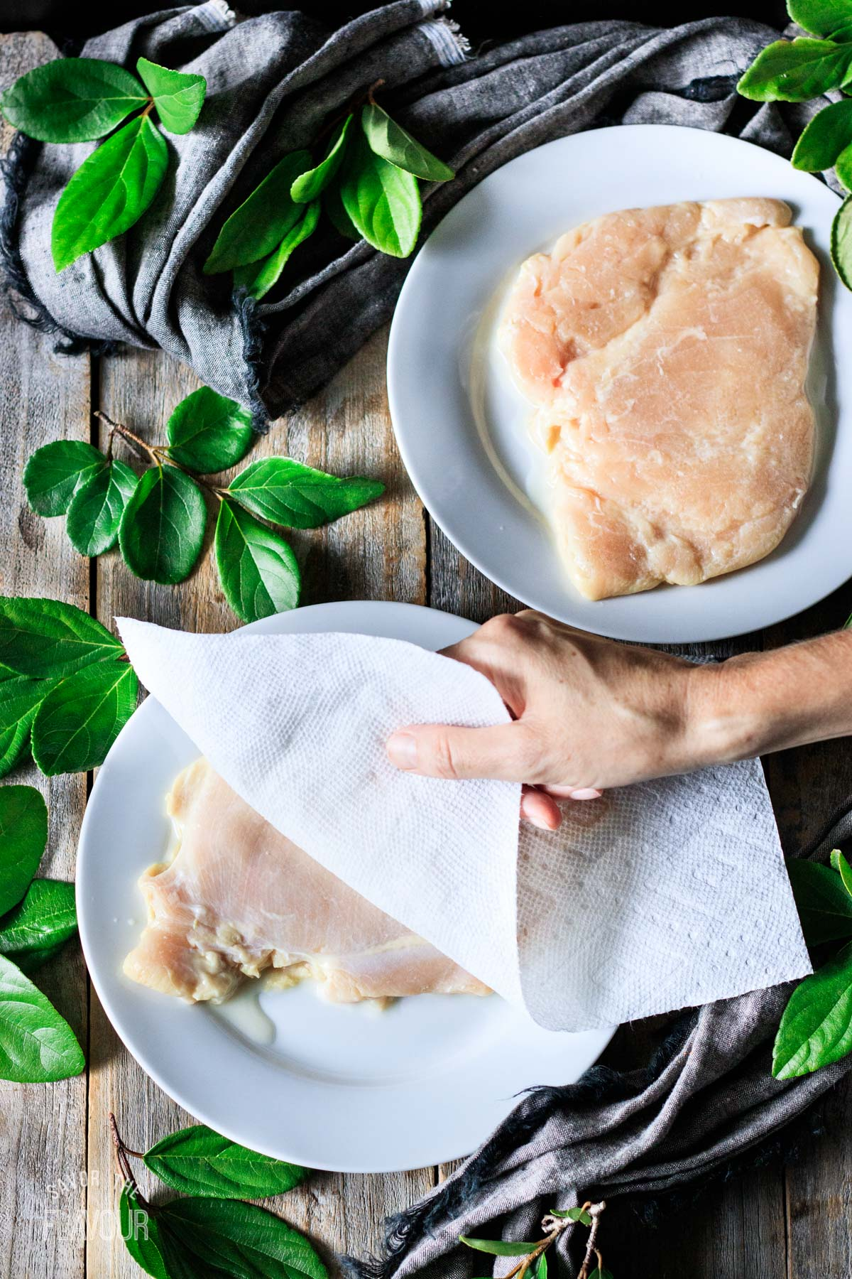 person patting dry chicken breasts with paper towel