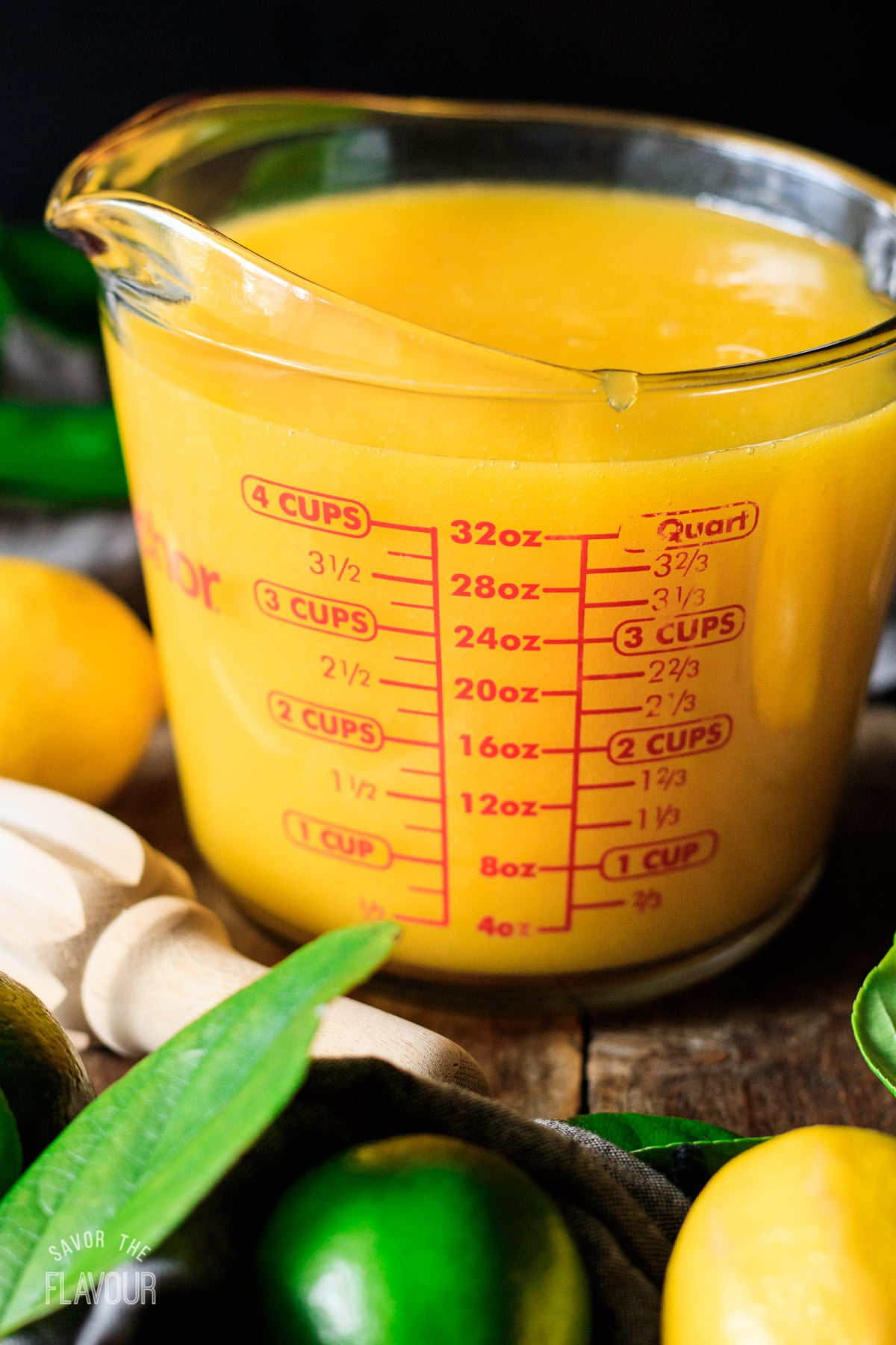 measuring mango lemonade in a glass measuring cup