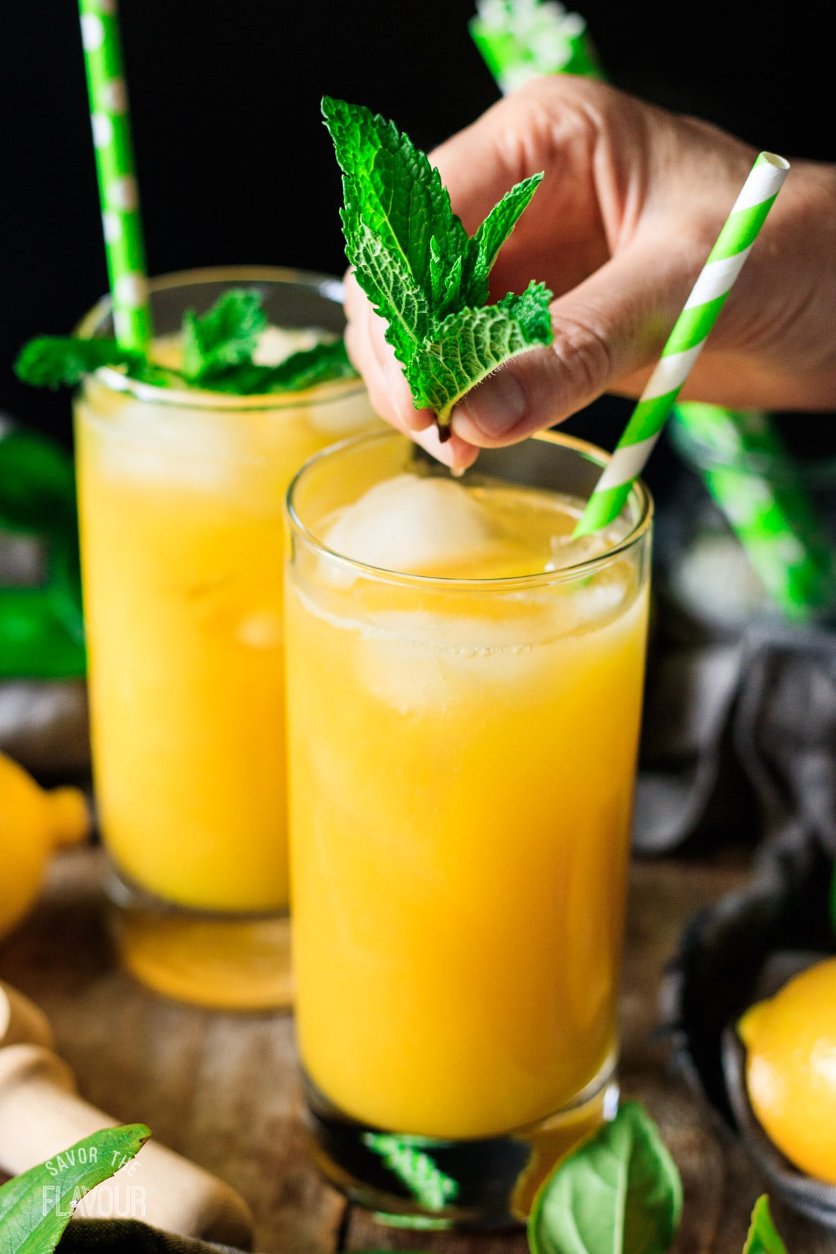 garnishing mango lemonade with a sprig of mint