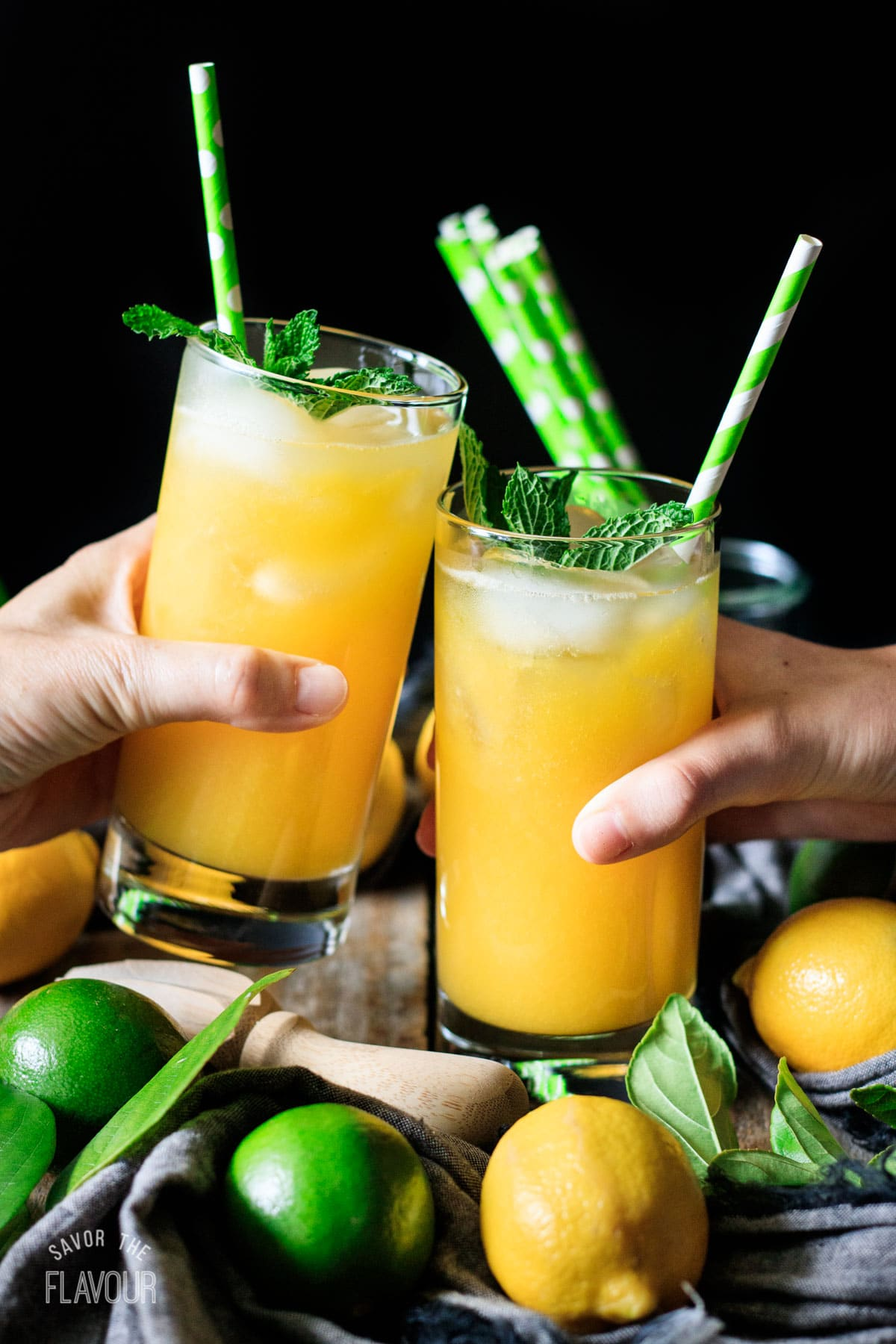 people doing a toast with two glasses of mango lemonade