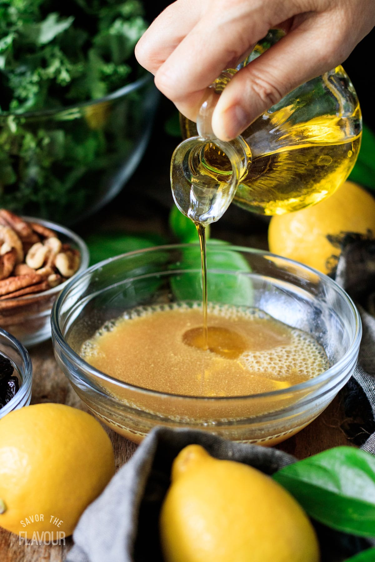 person pouring olive oil into the vinaigrette