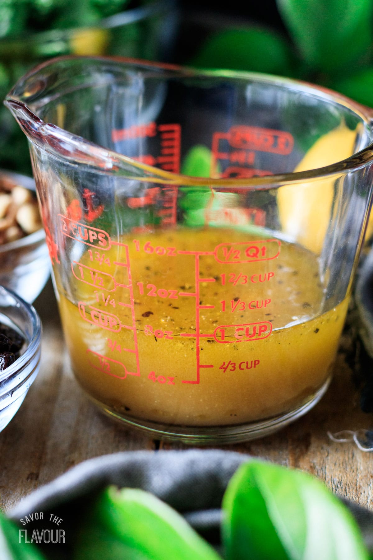 glass measuring cup filled with maple vinaigrette