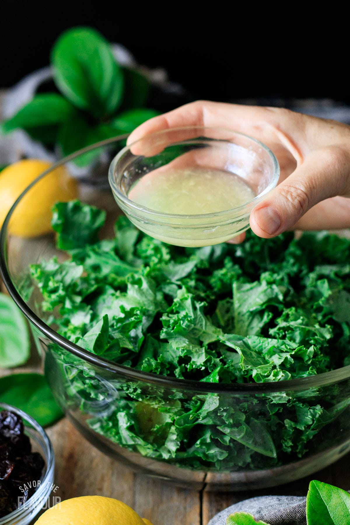 person holding a bowl of lemon juice over top of the kale