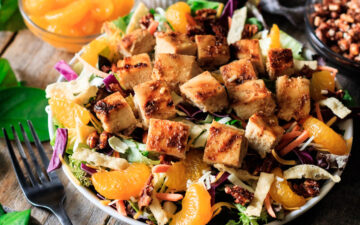 bowl of Asian chicken salad with bowls of topping