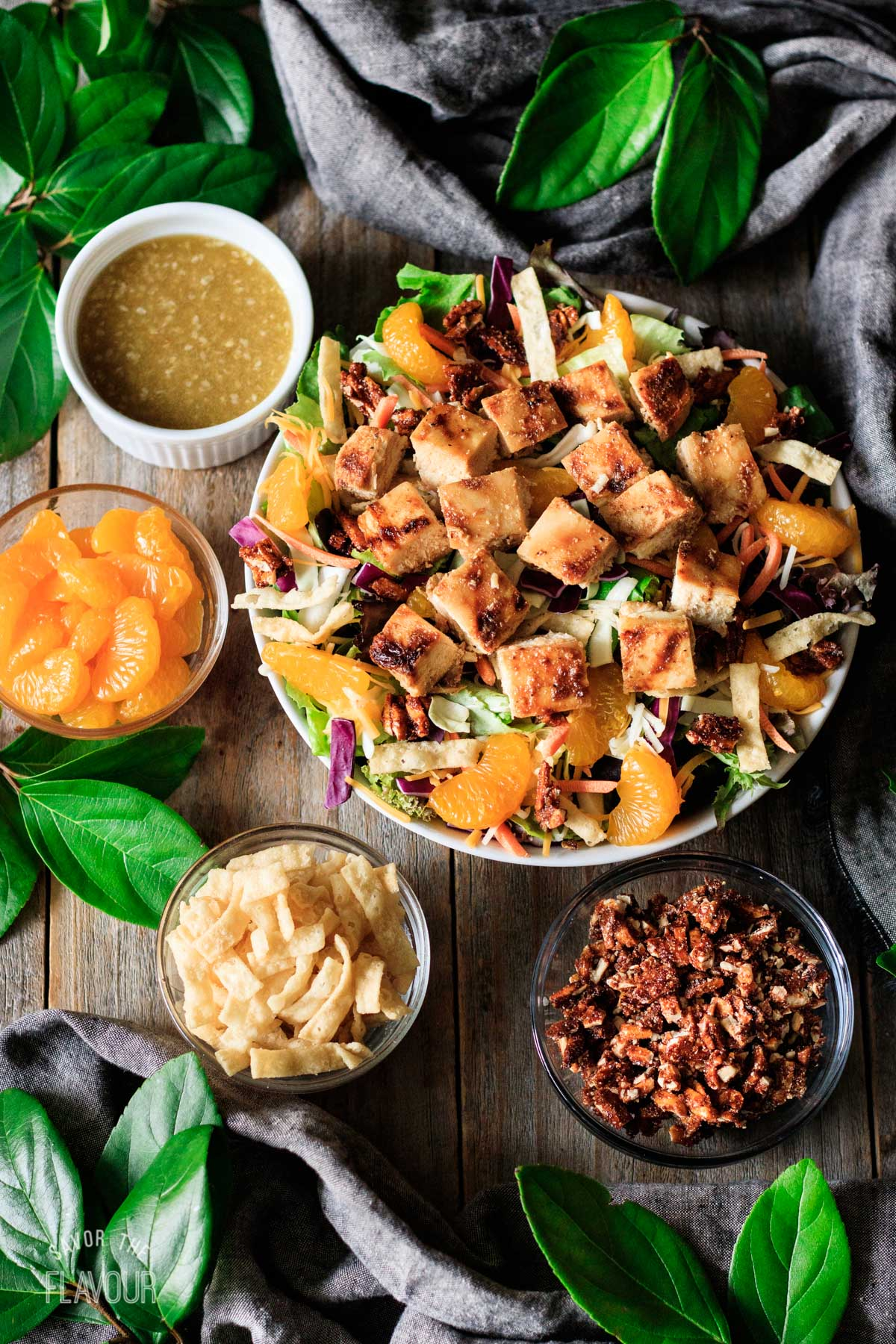 bowl of Asian chicken salad with bowls of dressing and toppings
