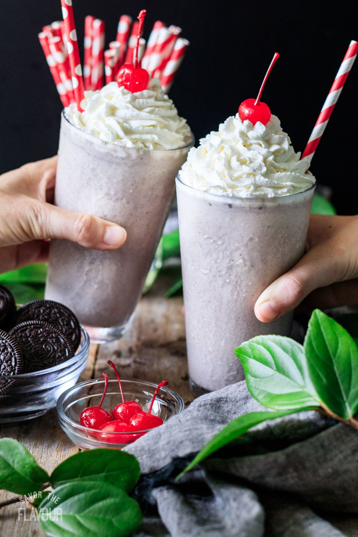 people doing a toast with two cookies and cream milkshakes