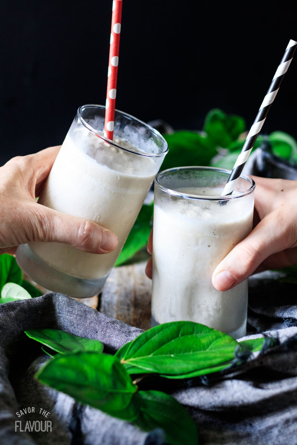 people doing a toast with two glasses of frosted coffee