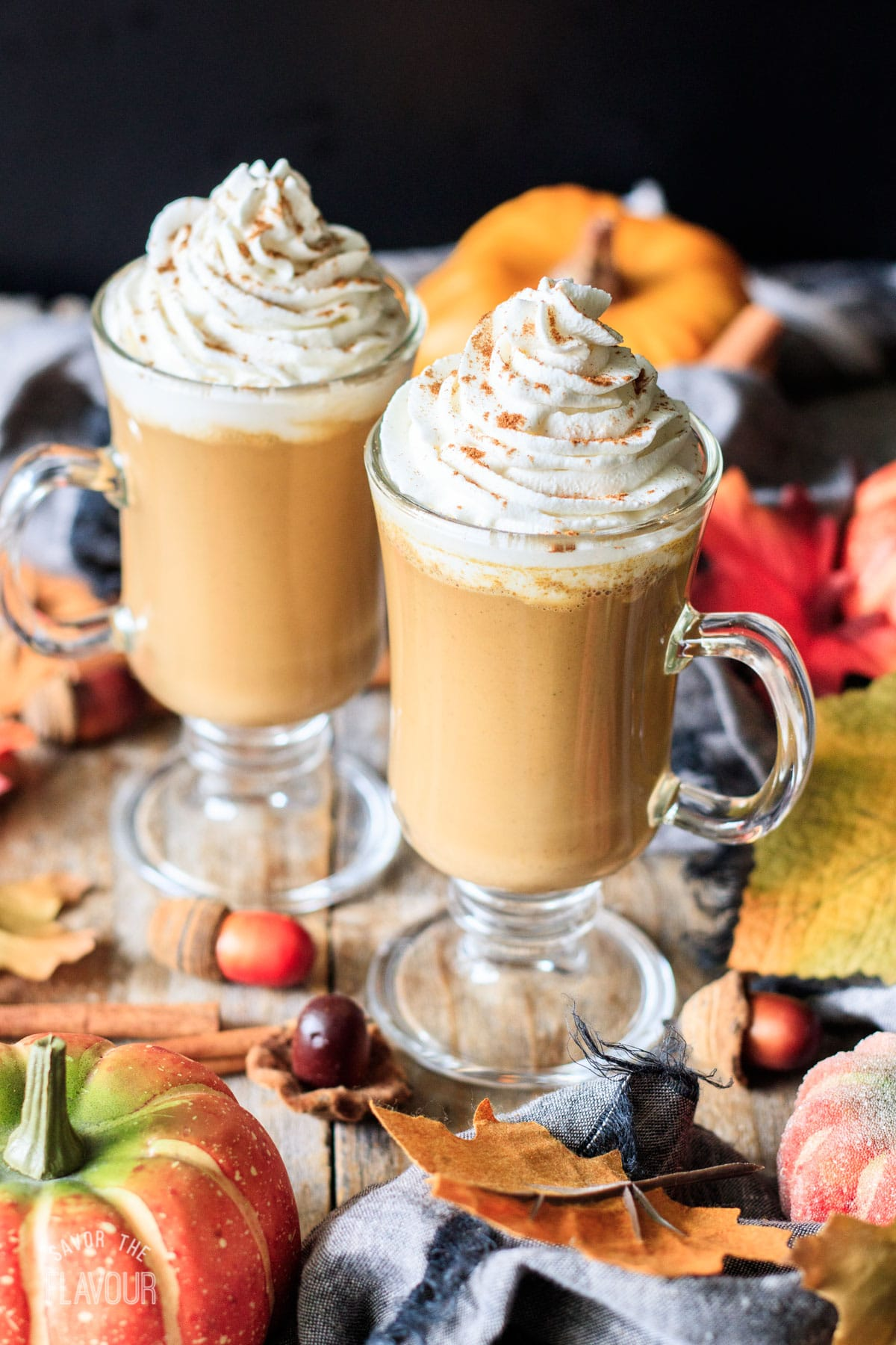two pumpkin spice lattes with whipped cream and spice