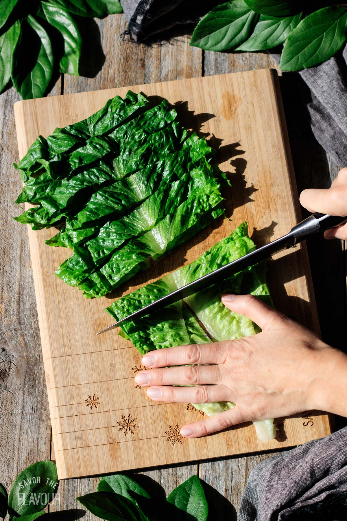 person chopping Romaine lettuce on a cutting board