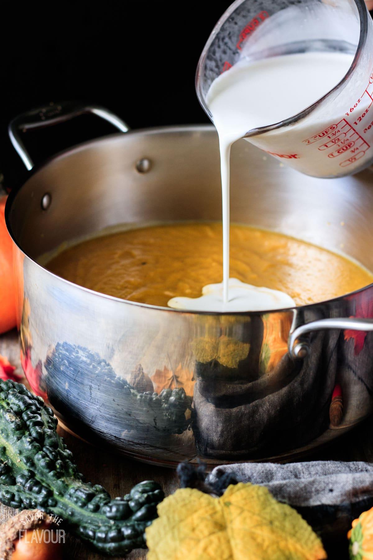pouring the coconut milk into the pot of pumpkin sweet potato soup