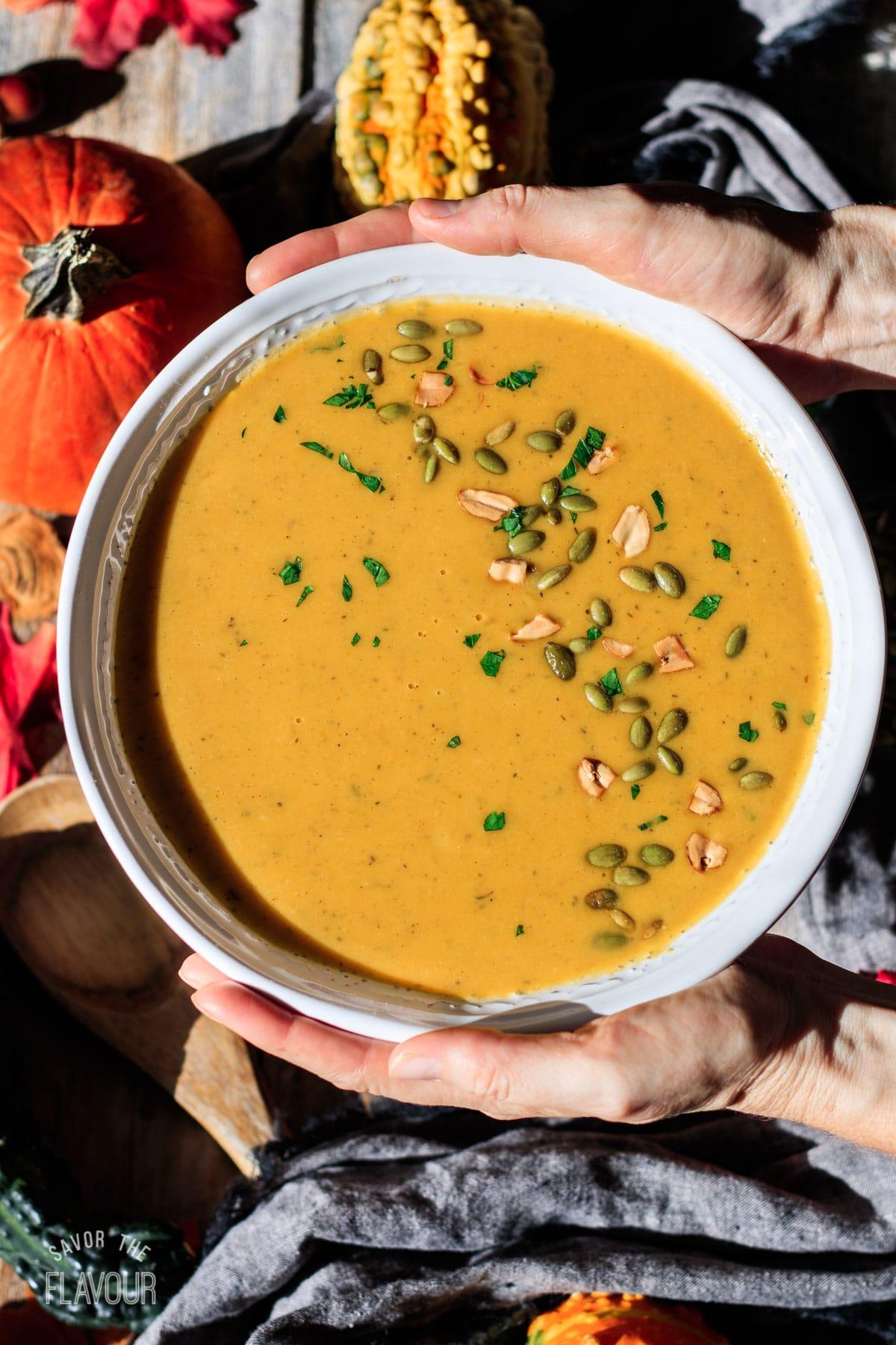 person holding a large white bowl of pumpkin sweet potato soup