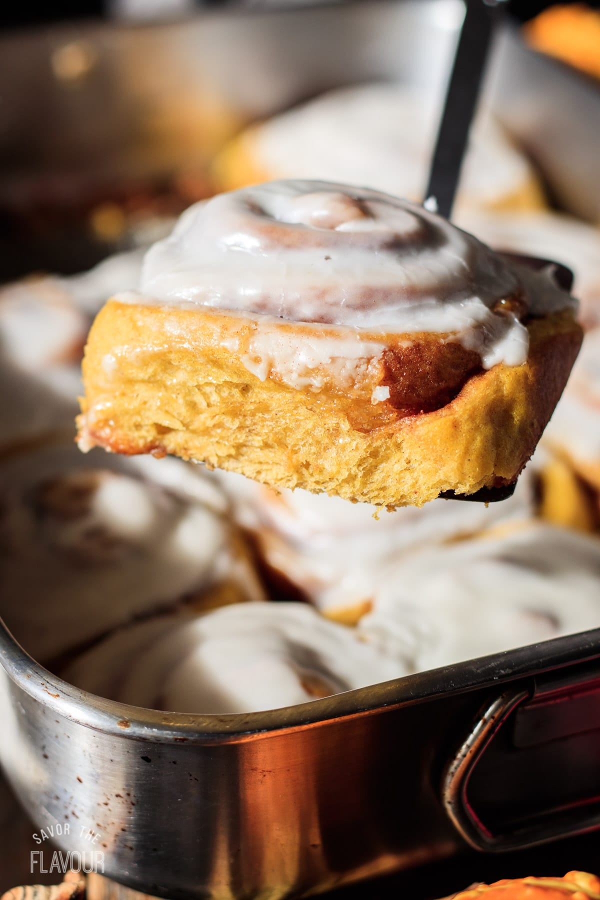 a pumpkin cinnamon roll being lifted from the pan with a spatula