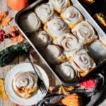 pan of vegan pumpkin cinnnamon rolls with fall leaves and gourds