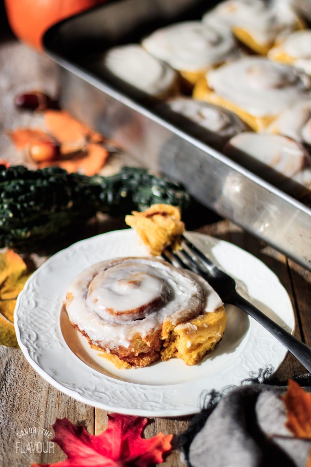 vegan pumpkin cinnamon roll on a white plate