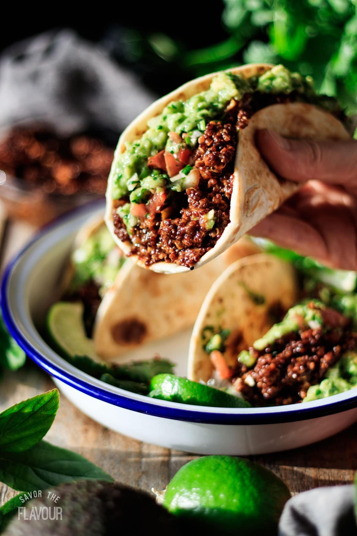 person holding a taco filled with vegan quinoa meat
