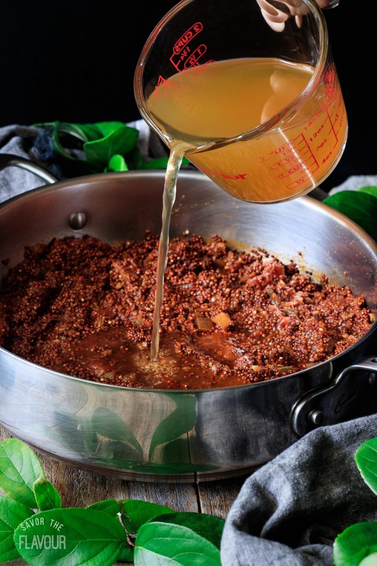 pouring chicken broth into the quinoa