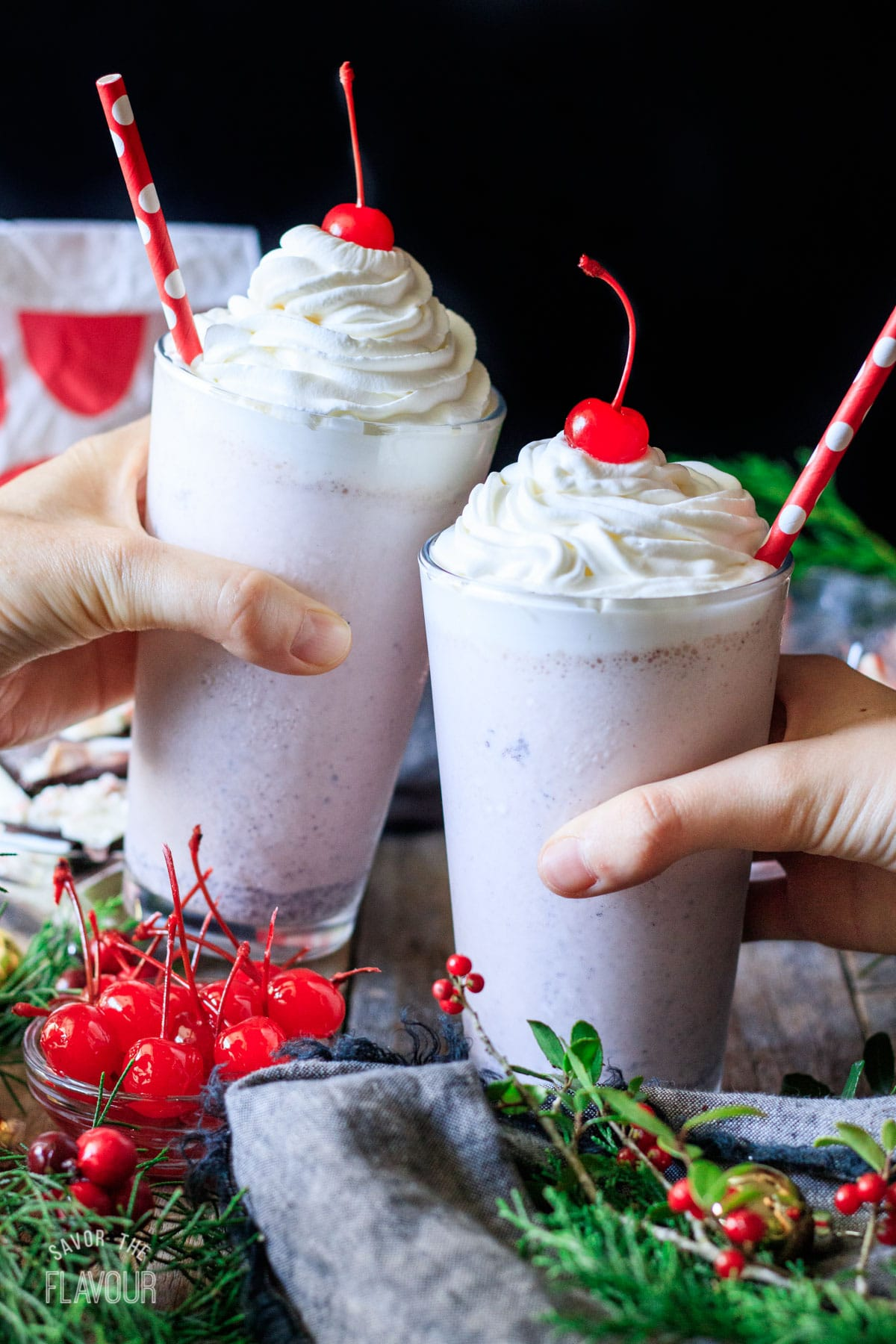 people doing a toast with two Chick-fil-A peppermint milkshakes