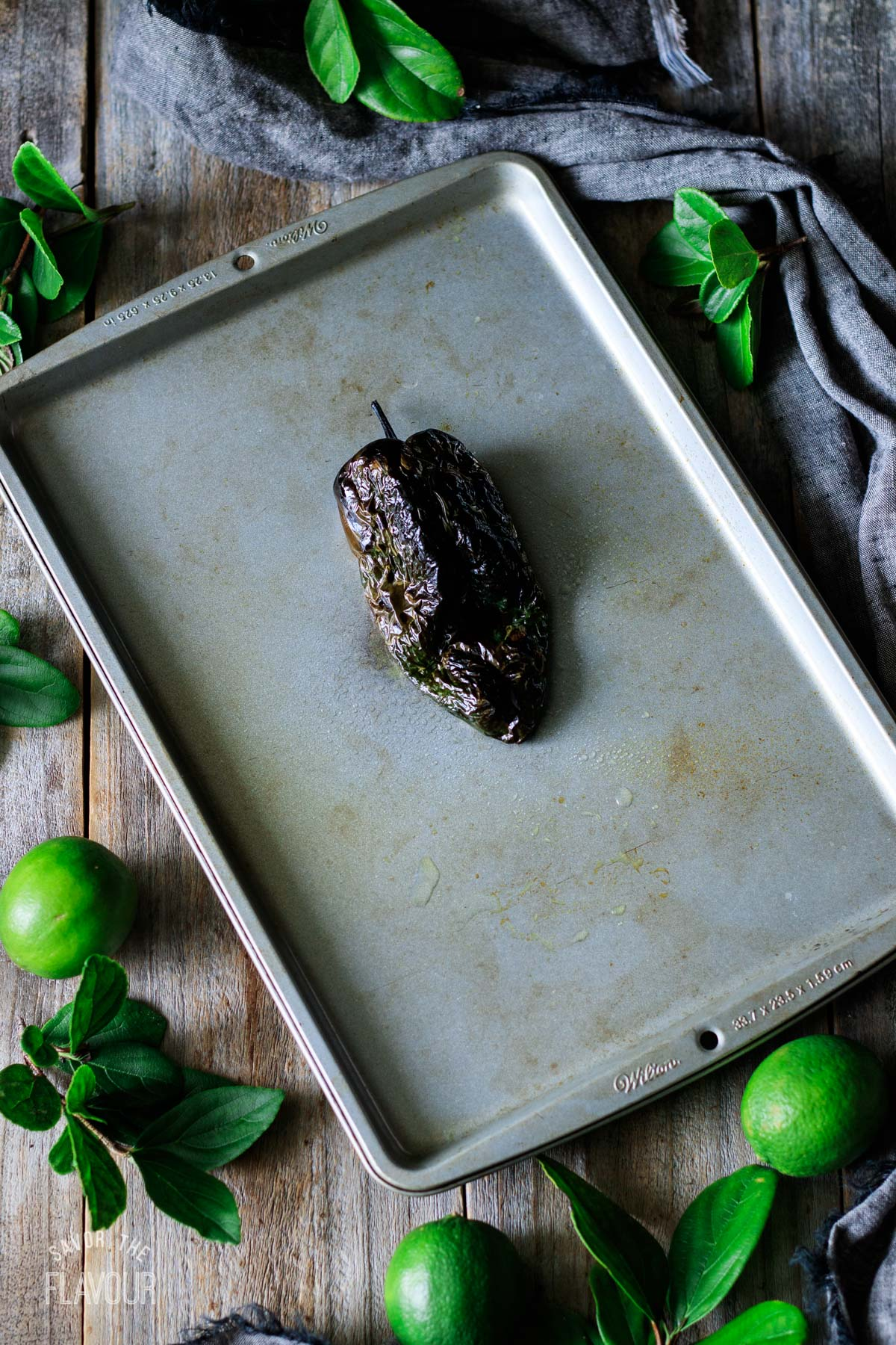 charred poblano pepper on a cookie sheet