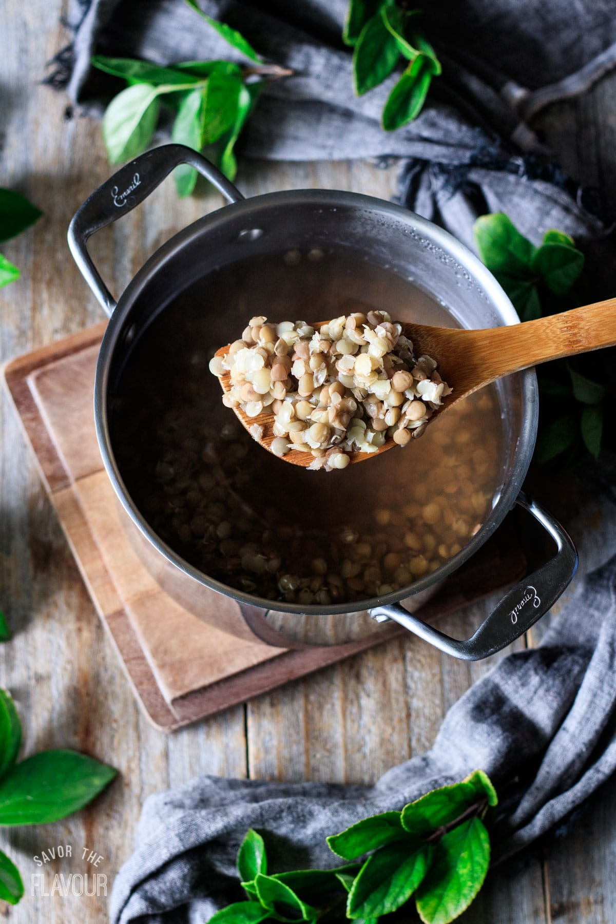 large wooden spoon full of cooked green lentils
