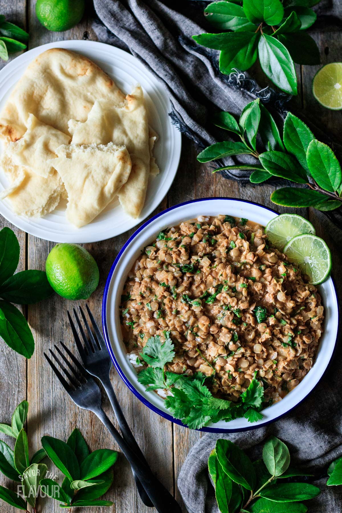 bowl of green curry lentils with a plate of naan bread