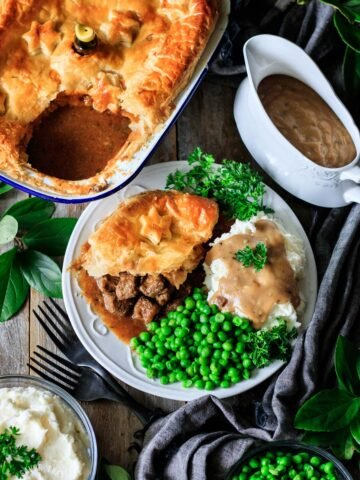 plate of Scottish steak pie with peas, mashed potatoes, and gravy