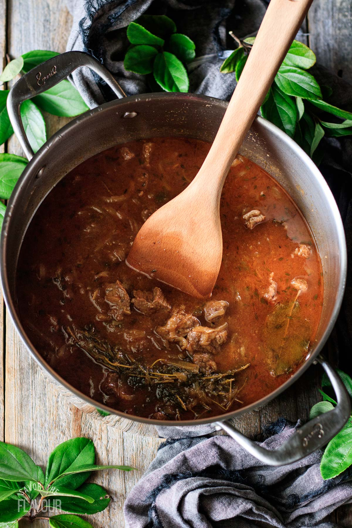 stirring cooked beef stew with a large wooden spoon