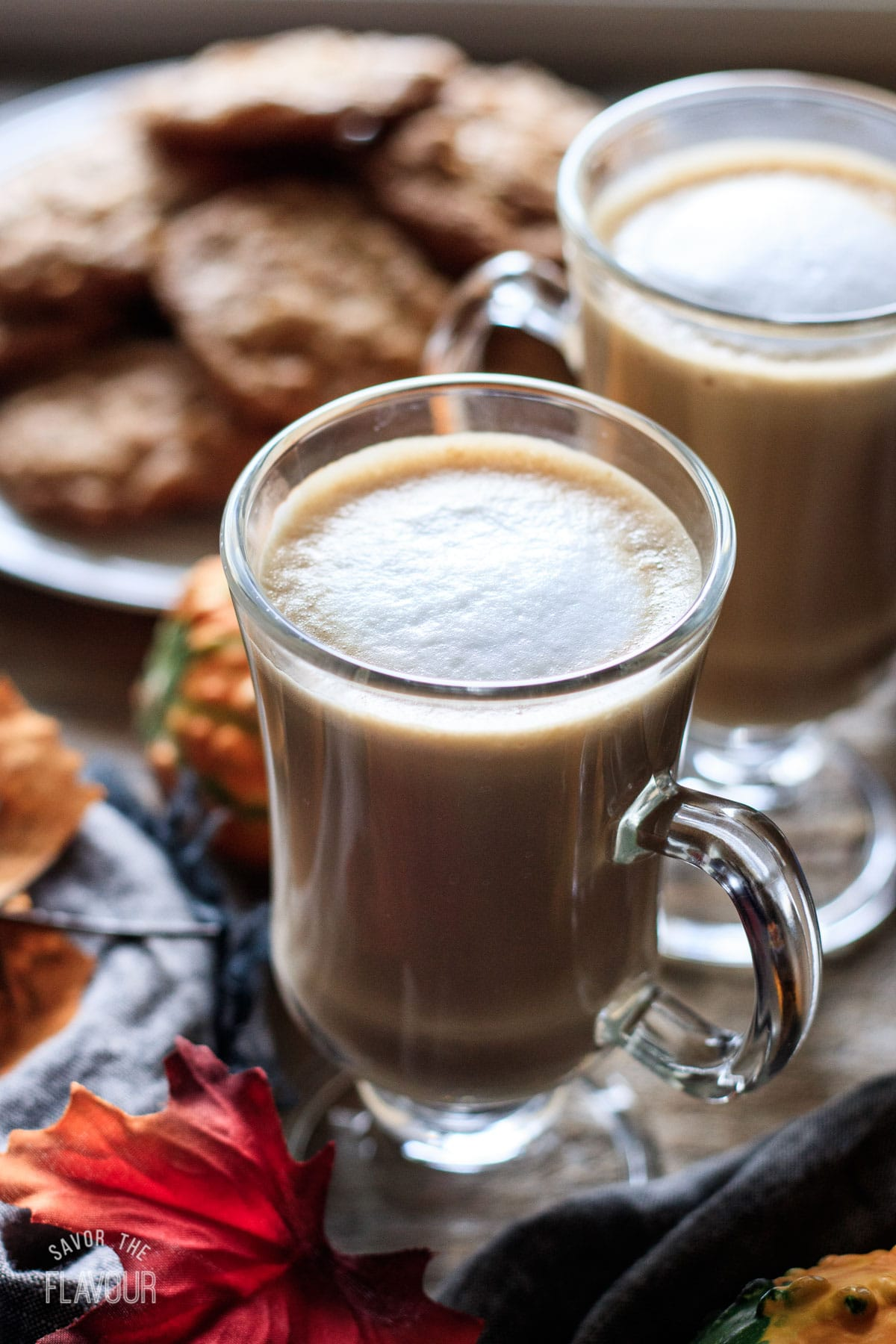 two glasses of flat white with a plate of cookies