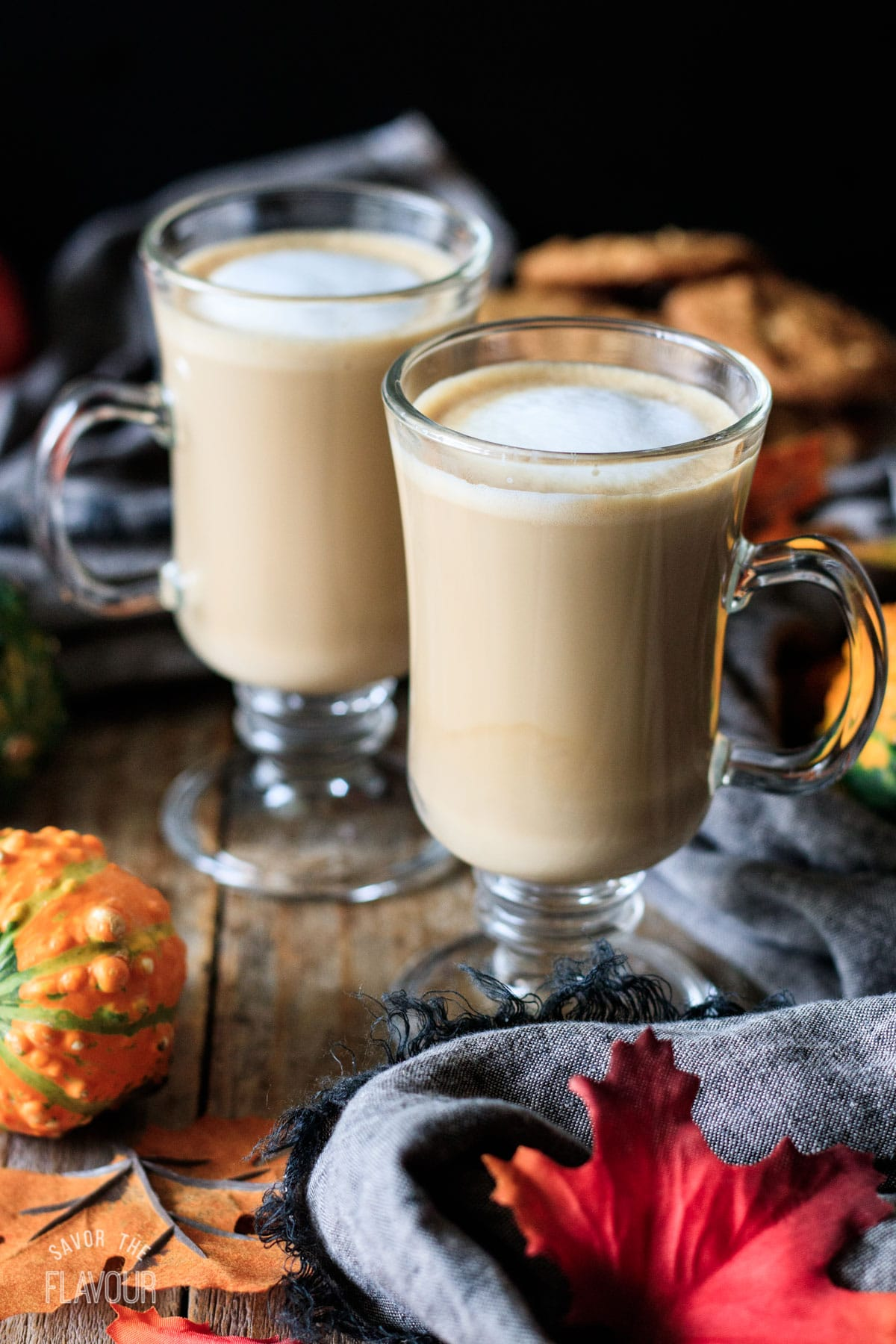 two glass mugs of flat white with fall leaves and gourds